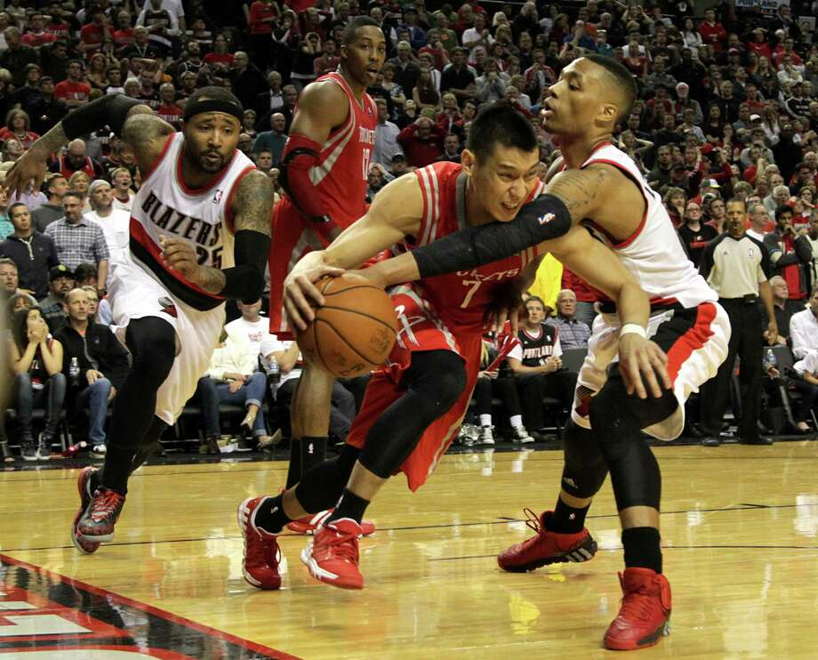 Trail Blazers guard Damian Lillard (0) reaches in to try to steal the ball from Rockets guard Jeremy Lin (7) in the fourth quarter. Lin committed three turnovers in the game. Photo: James Nielsen, Staff / © 2014  Houston Chronicle