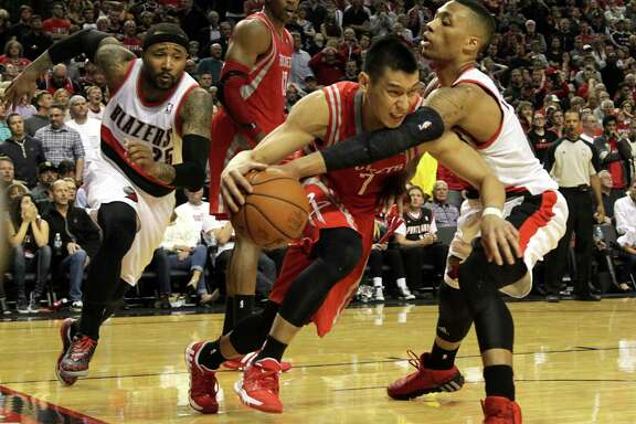 Trail Blazers guard Damian Lillard (0) reaches in to try to steal the ball from Rockets guard Jeremy Lin (7) in the fourth quarter. Lin committed three turnovers in the game.