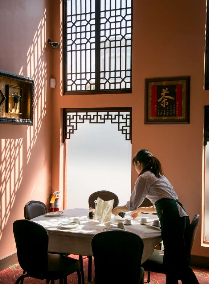 A server sets a table at Hong Kong Lounge 2 in San Francisco. Photo: John Storey, Special To The Chronicle