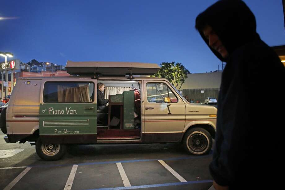 Sitting in a 1983 Ford Econoline he calls the Piano Van, Chris Stroffolino plays a song for a lone listener in the Safeway on Mission Street in San Francisco. Photo: Mike Kepka, The Chronicle