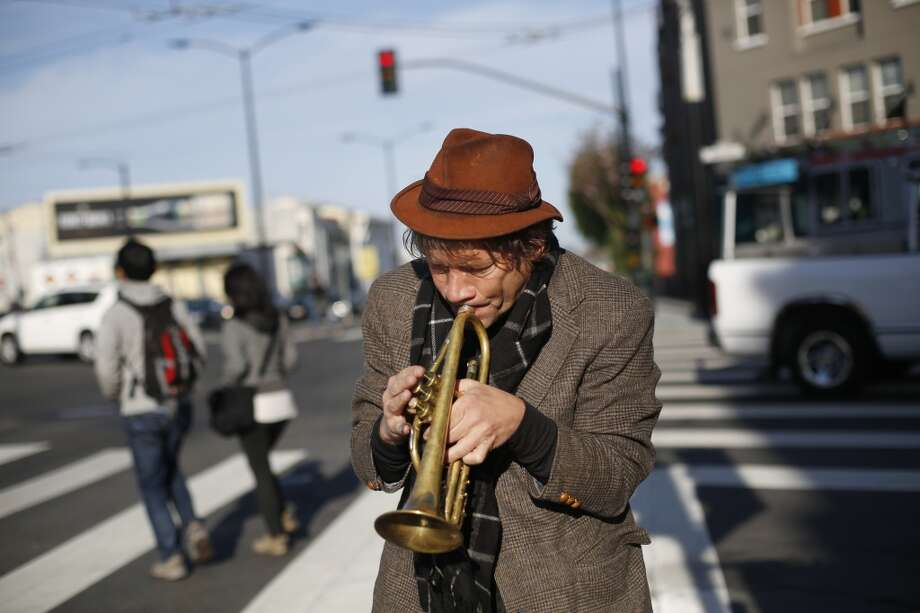 Seeking musical inspiration from his trumpet, Chris Stroffolino steps away from his Piano Van on Mission Street in San Francisco. Photo: Mike Kepka, The Chronicle