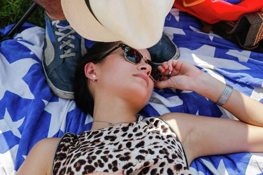 Henry Aerins (not shown) uses his hat to fan some air on Melanie Ku, of Hong Kong, for a little relief from the warm temperatures. This was Ku's first visit to the festival.(AP Photo/Doug Parker) Photo: Doug Parker, Getty / FR 170928AP