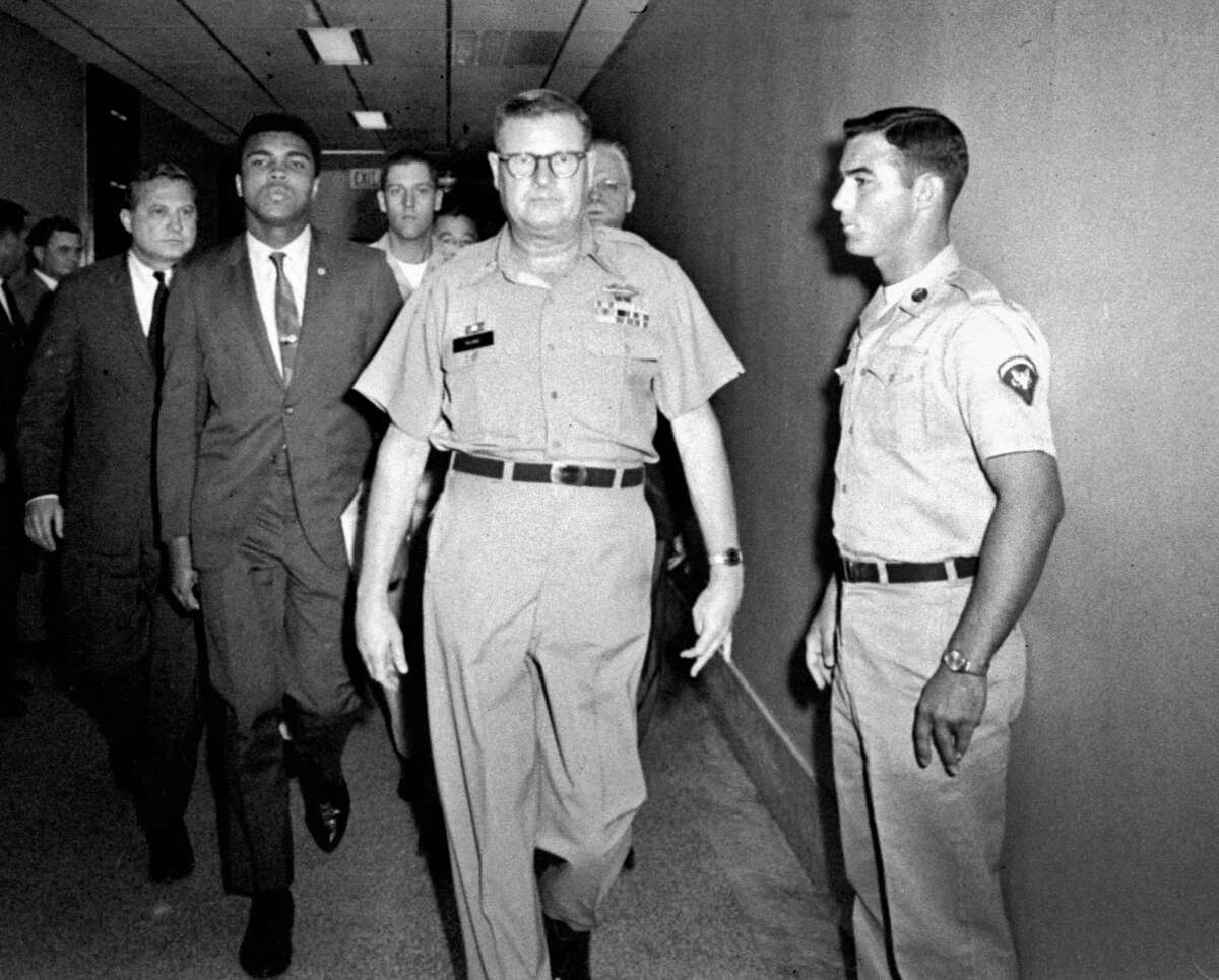 In this April 28, 1967 file photo, heavyweight boxing champion Muhammad Ali is escorted from the Armed Forces Examining and Entrance Station in Houston by Lt. Col. J. Edwin McKee, commandant of the station, after Ali refused Army induction. Ali says he was a conscientious objector who would not serve in the Army of a country that treated members of his race as second-class citizens.