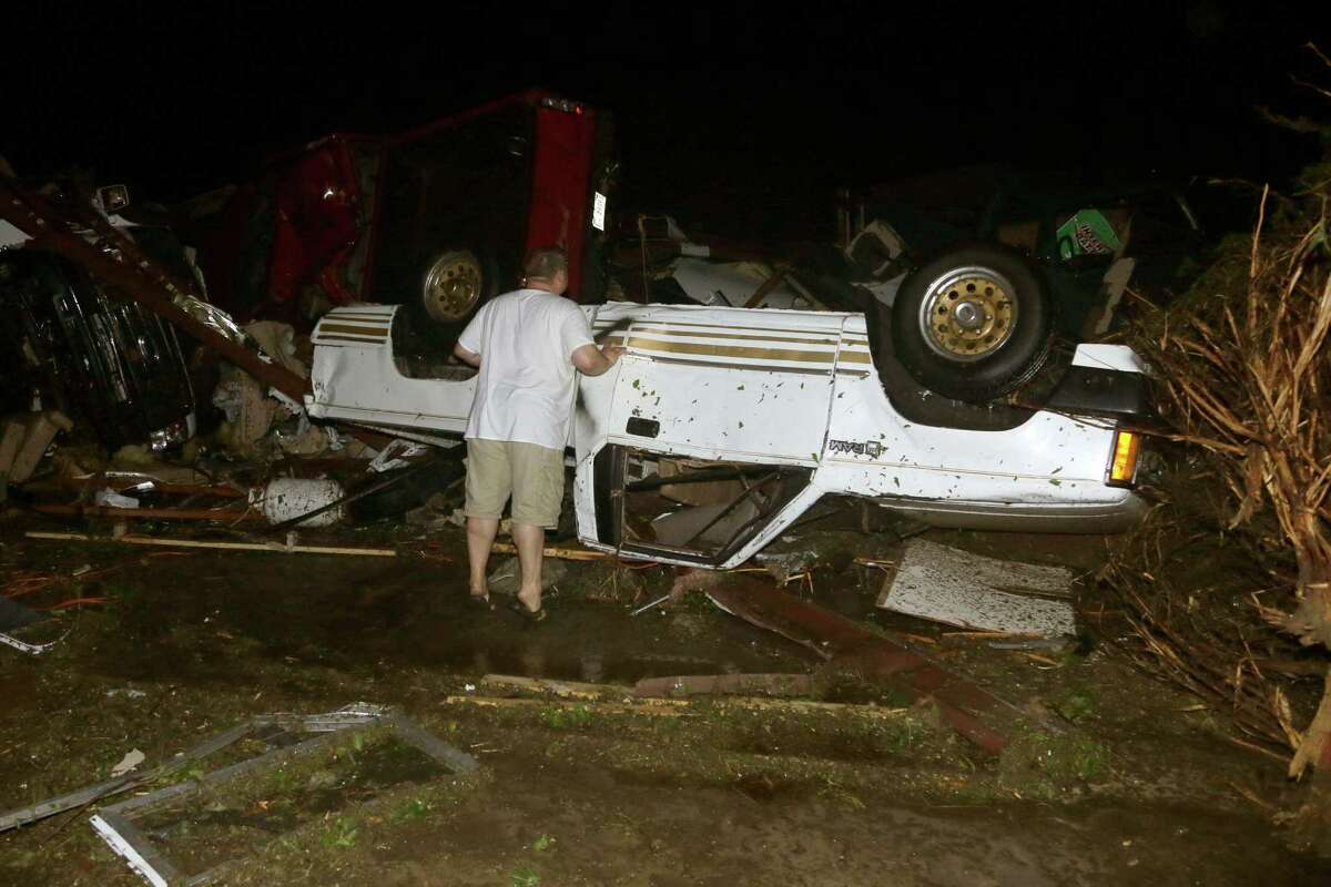 John Ward, an automobile and RV dealer, looks at tornado damage to one of his trucks in Mayflower, Ark., Sunday, April 27, 2014. At least 16 people died Sunday night in Arkansas as a tornado carved an 80-mile path of destruction. (AP Photo/Danny Johnston) ORG XMIT: ARDJ103