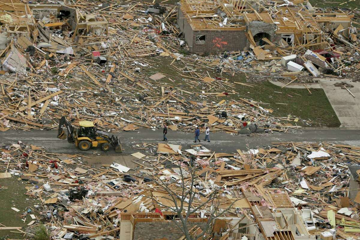 People walk between two destroyed houses in Mayflower, Ark., Monday, April 28, 2014, after a tornado struck the town late Sunday. A tornado system ripped through several states in the central U.S. and left at least 17 dead in a violent start to this year's storm season, officials said. (AP Photo/Danny Johnston) ORG XMIT: ARDJ105