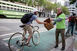 San Francisco Bicycle Coalition member and volunteer, Michael Helquist, hands out oranges to bicyclists on Market Street during Bike to Work Day.