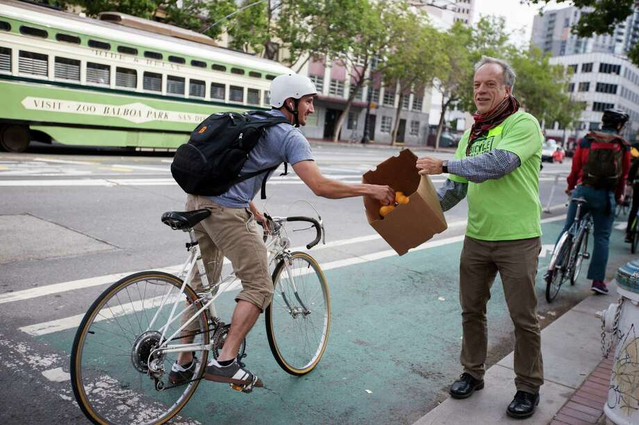 San Francisco Bicycle Coalition member and volunteer, Michael Helquist, hands out oranges to bicyclists on Market Street during Bike to Work Day. Photo: Myleen Hollero / Myleen Hollero / / ONLINE_YES