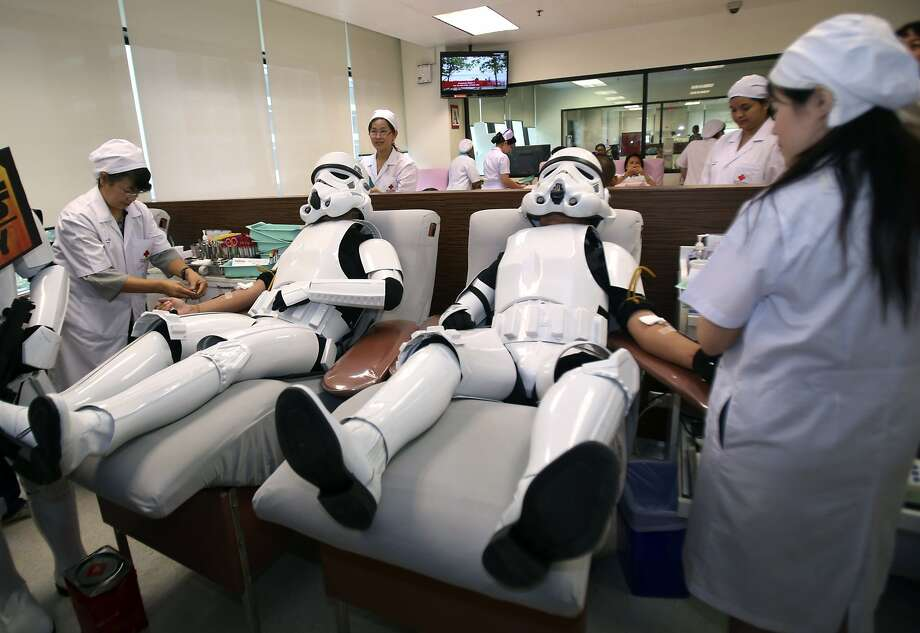 Udomsak Ratanotayo, left, and Suttinan Boonsomkiat wear storm trooper costumes while donating blood at the Thai Red Cross in Bangkok, Thailand on Monday, April 28, 2014. Thai Star Wars fans will donate blood and give toys at an orphanage as part of a promotional campaign. (AP Photo/Sakchai Lalit) Photo: Sakchai Lalit, Associated Press