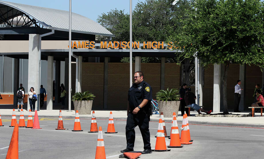 A police officer walks in the parking lot of Madison High School Monday April 28, 2014 after a student was taken into custody who allegedly had weapons in his backpack. No one was injured and many parents arrived to take their kids home from school. Photo: JOHN DAVENPORT, San Antonio Express-News / ©San Antonio Express-News/John Davenport