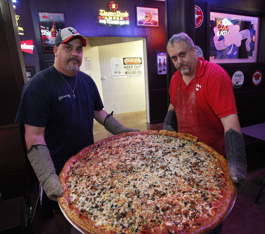 Brothers Art (left) and Brian Lujan show one of the famous 42-inch pizzas at Big Lou's Pizza. / SAN ANTONIO EXPRESS-NEWS