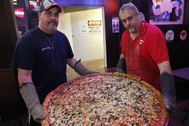 Brothers Art (left) and Brian Lujan show one of the famous 42-inch pizzas at Big Lou's Pizza.