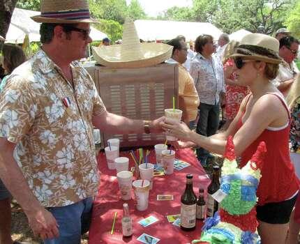Rob Finney (left) hands a Don Robertos michelada to Sara Davis at the Olmos Park Fiesta Frolic on Sunday at Alameda Circle. Photo: Edmond Ortiz / Alamo Heights Wee