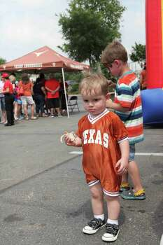 Dean Krupka, 2, enjoys a treat at the University Co-op's Fiesta celebration Saturday at the Alamo Quarry Market. The local Co-Op's annual Fiesta-themed event included free refreshments, entertainment, and an appearance by the Texas Longhorns Marching Band. Photo: Mary Candee / For Alamo Heights