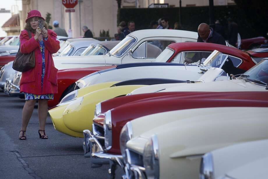 Donna Huggins snaps a picture of the vintage cars on display in front of the Fairmont San Francisco on Nob Hill. Photo: Mike Kepka, The Chronicle