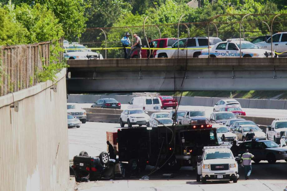 A car apparently drove off Main Street, broke through a barrier and landed on the northbound lanes of Interstate 45 below. (Johnny Hanson / Houston Chronicle) Photo: Johnny Hanson / Houston Chronicle