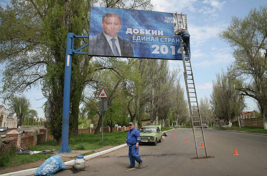 Workers install a billboard for Ukrainian presidential candidate Mikhail Dobkin lin Atemivsk, Ukraine. Ukraine will hold its presidential election on May 25. Photo: Scott Olson / Getty Images / 2014 Getty Images