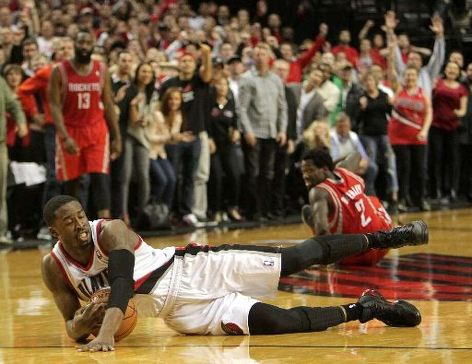 Trail Blazers guard Wesley Matthews falls on a loose ball after knocking it away from Rockets guard Patrick Beverley during the overtime of Game 4. Photo: James Nielsen, Houston Chronicle