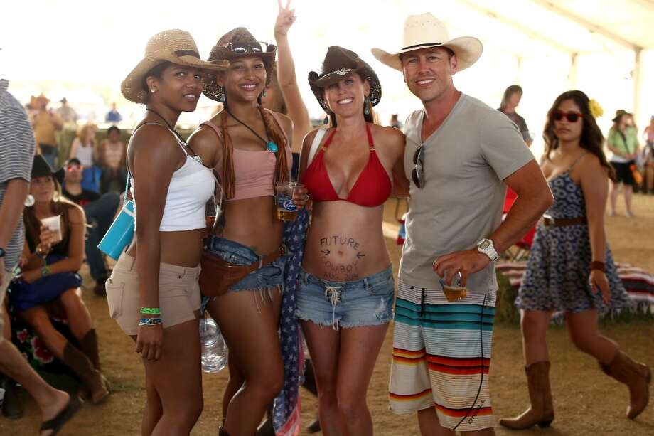 We often see bikinis at music festivals, but rarely do we see men in board shorts. Also, this lady's belly button is  going to turn into a cowboy in August. We assume it will be on the YouTube. Photo: Christopher Polk, Getty Images For Stagecoach