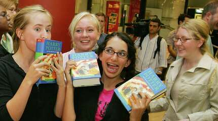 "LONDON, UNITED KINGDOM:  Heidi Hanson (L), 17 of Salt Lake City, USA kisses her copy of ""Harry Potter and the half blood Prince"" flanked by her sisters Elise (R), Andrea (2ndL) and friend Marjaan Alcaioiat after queuing for hours outside Waterstone's book store in Picadilly circus for the long awaited sixth book in the Harry Potter series that went on sale in London, 16 July 2005.  The much-anticipated book went on sale across the world at midnight UK time 16 July amid upprecedented fanfare. AFP PHOTO/ODD ANDERSEN"
