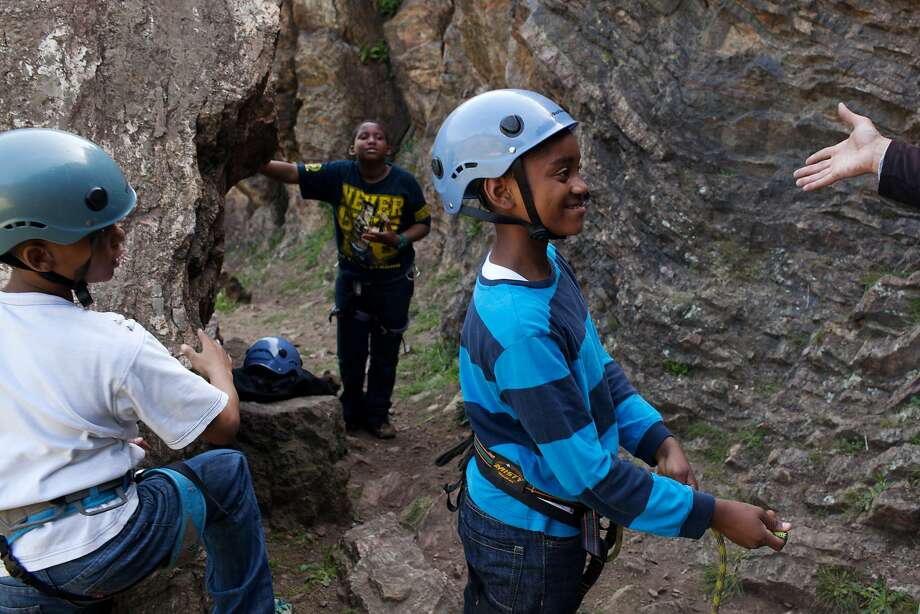Jovian (left), 10, James, 12, and James, 11, listen to therapist Clifton Hicks before a rock-climbing exercise in S.F.'s Glen Canyon Park. The adventure-based psychotherapy program is specifically designed for youths. Photo: Tim Hussin, Special To The Chronicle