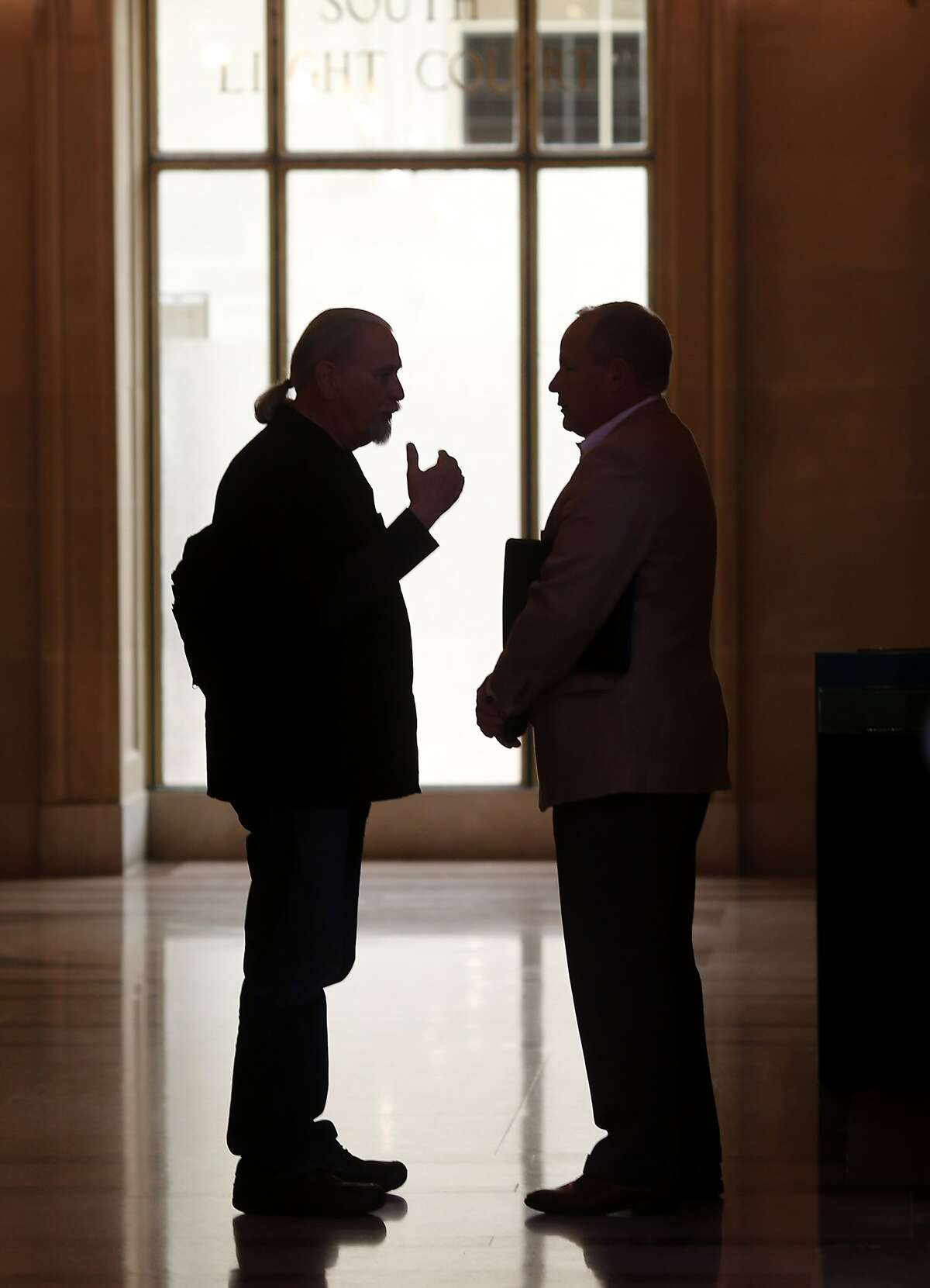 Calvin Welch, a housing activist, (left) and Dale Carlson, a public relations executive, talked while waiting for their friend in City Hall before visiting some Supervisors. A group of neighborhood activists are organizing a ballot initiative to rein in short-term rentals like Airbnb in San Francisco, Calif.