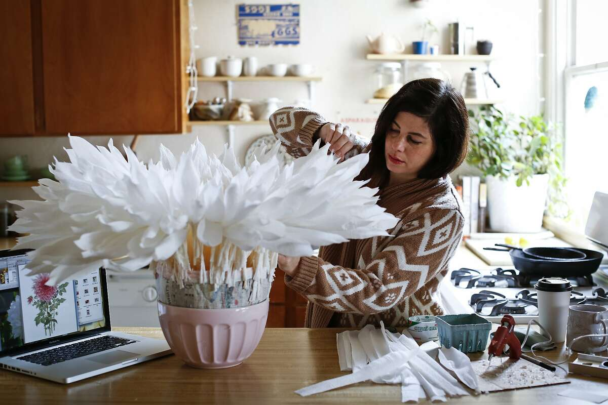 Tiffanie Turner looks over one of her works in progress, a crepe paper dahlia, in her San Francisco, Calif., home on Thursday, April 24, 2014. Turner is preparing for a show at Rare Device on Divisadero street which opens in May.