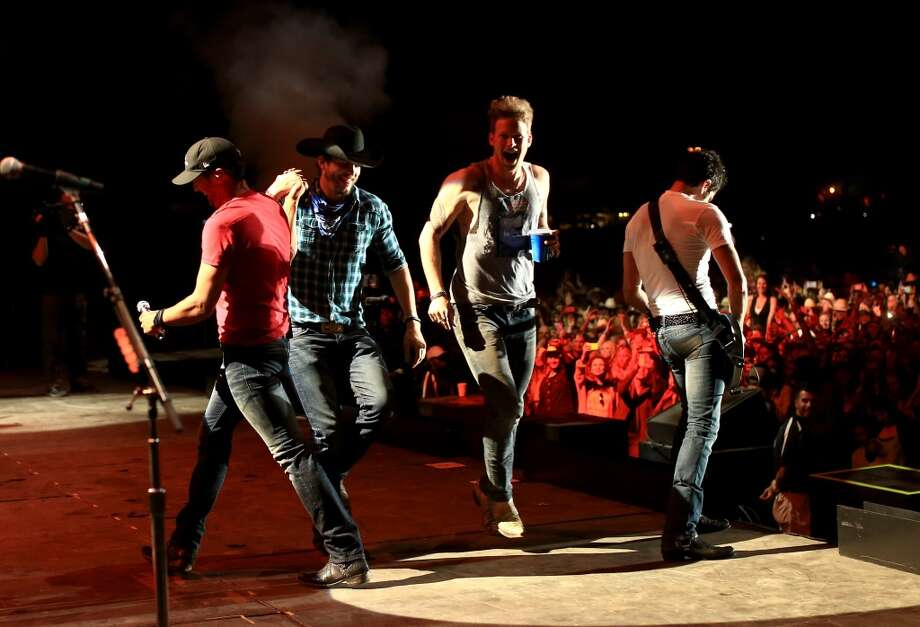 (L-R) Musician Luke Bryan, actor Ashton Kutcher and musician Brian Kelley onstage during day 3 of 2014 Stagecoach: California's Country Music Festival at the Empire Polo Club on April 27, 2014 in Indio, California. Photo: Christopher Polk, Getty Images For Stagecoach