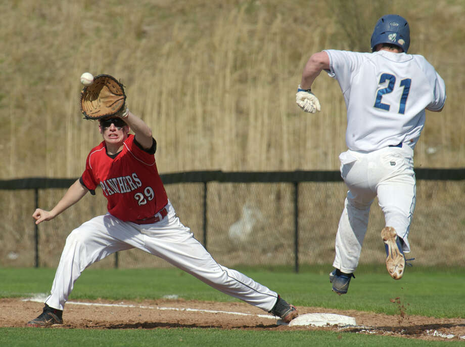 Pomperaug's Samuel Rubinstein, #29, reaches for the throw to first while Newtown's Sam Czel, #21, tries to beart the throw, during the Pomperaug and Newtown boys SWC high school baseball game in Newtown, Conn, on Monday, April 28, 2014. Czel was called safe. Photo: H John Voorhees III / The News-Times Freelance