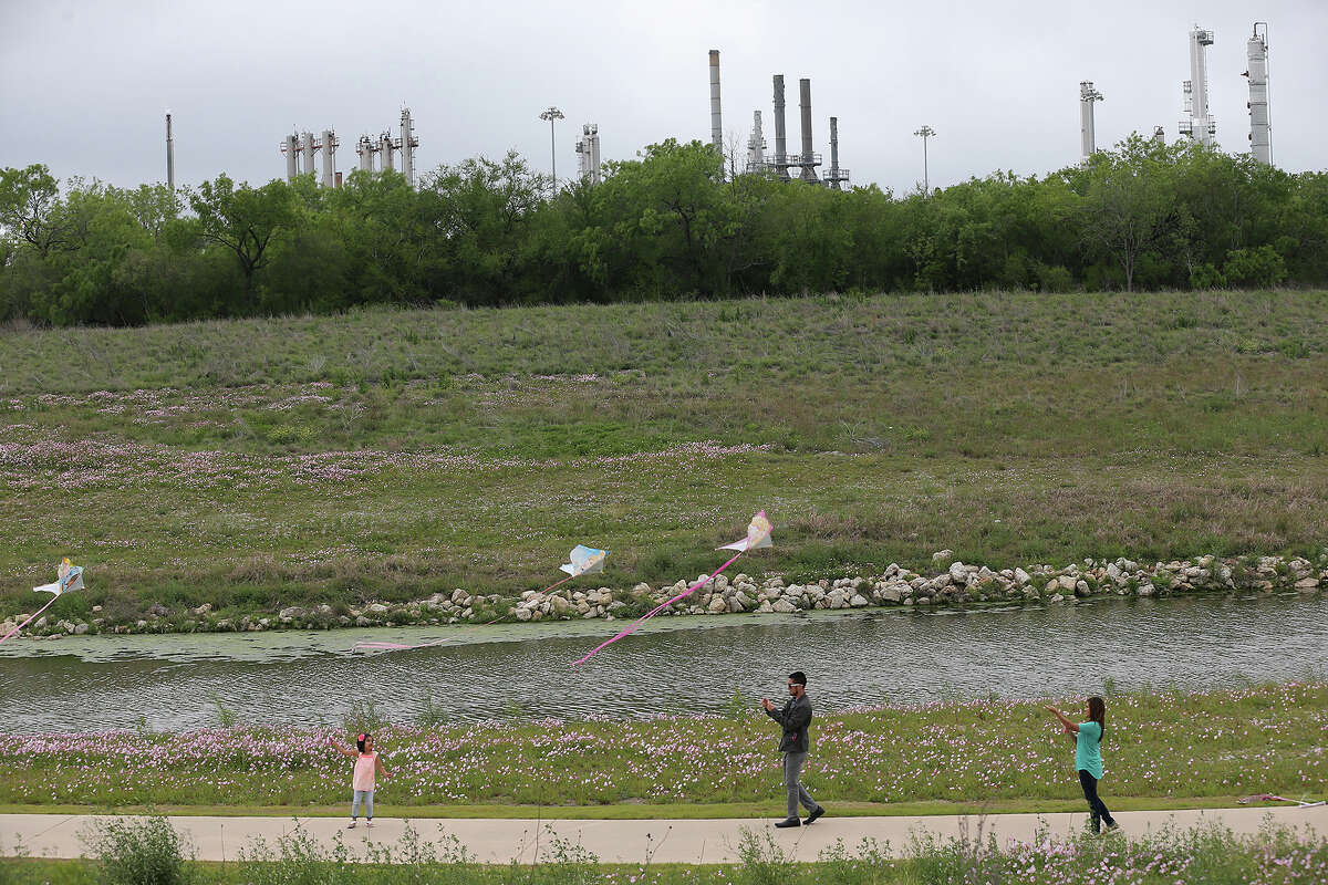 By the steel structures of Calumet Specialty Products Partners plant, Hailey Carrijo, 5, left, flies kites with her mother, Rebekah Martinez, 25, right, and her mothers boyfriend, Louie Garcia, 28, along the Mission Reach of the San Antonio River, Thursday, April 17, 2014.