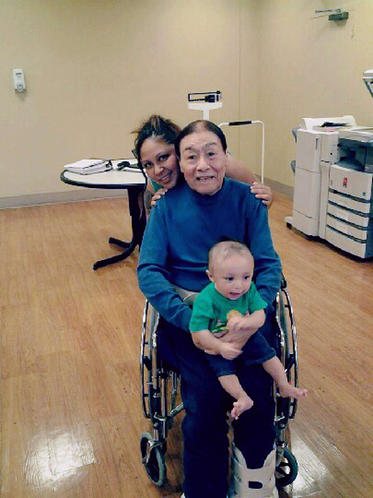 This image provided by Sergio Godoy shows his sister Janet Godoy, rear, grandfather Antonio Acosta and Janet Godoy's son Juan Manuel Gonzalez. Police say a resident of a Houston nursing home will face capital murder charges for using the armrest of his wheelchair to beat two of his roommates, including Acosta, to death. (AP Photo/Sergio Godoy)