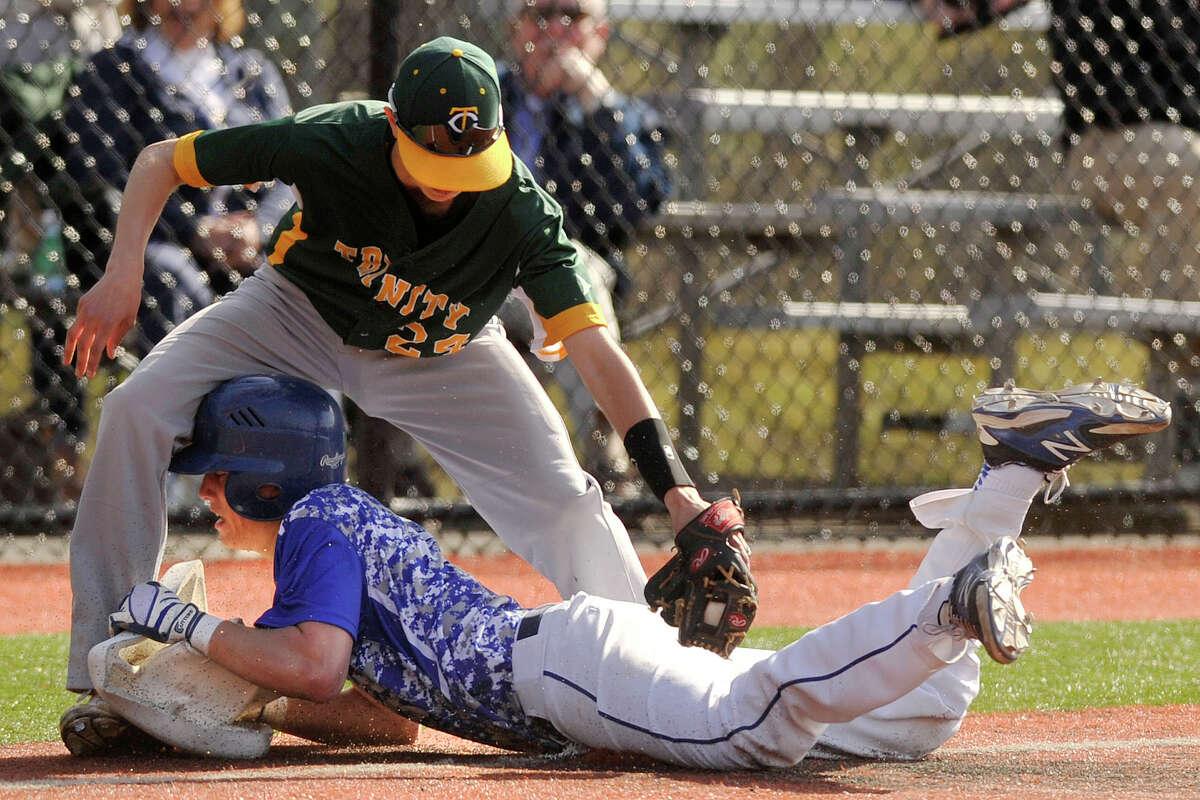 Darien's Daly Hebert pulls up third base after sliding in safely under the tag of Trinity Catholic third baseman Matt Fraioli during their baseball game at Darien High School in Darien, Conn., on Monday, April 28, 2014. Darien won, 18-6.