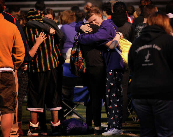 Students hug on the football field during the vigil for slain student Maren Sanchez at Jonathan Law High School in Milford, Conn. on Monday, April 28, 2014. Photo: Brian A. Pounds / Connecticut Post