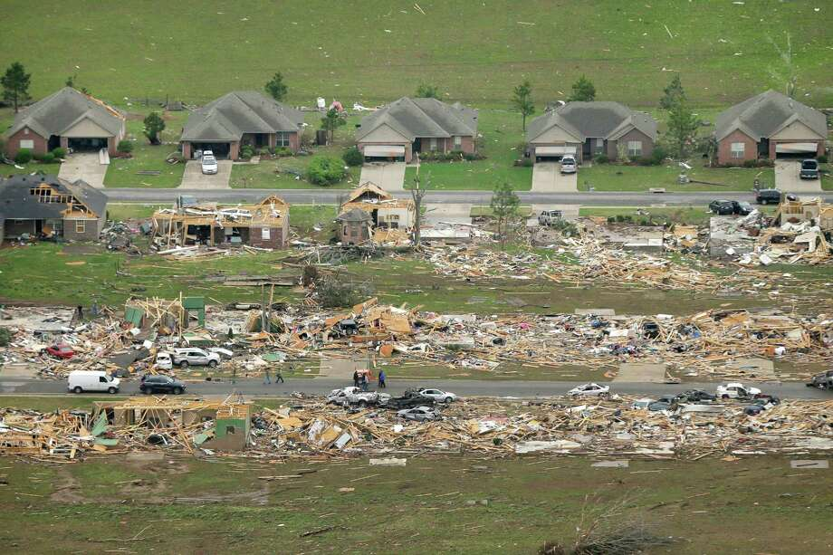A row of lightly damages houses, top, face destroyed homes in a Vilonia, Ark., neighborhood Monday, April 28, 2014 after a tornado struck the town late Sunday, killing at least 16 people.   (AP Photo/Danny Johnston) ORG XMIT: ARDJ107 Photo: Danny Johnston / AP