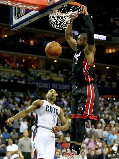 The Bobcats' Gerald Henderson can only watch as Heat guard Dwyane Wade dunks en route to scoring 15 points Monday night in Charlotte. Photo: Streeter Lecka / Getty Images / 2014 Getty Images