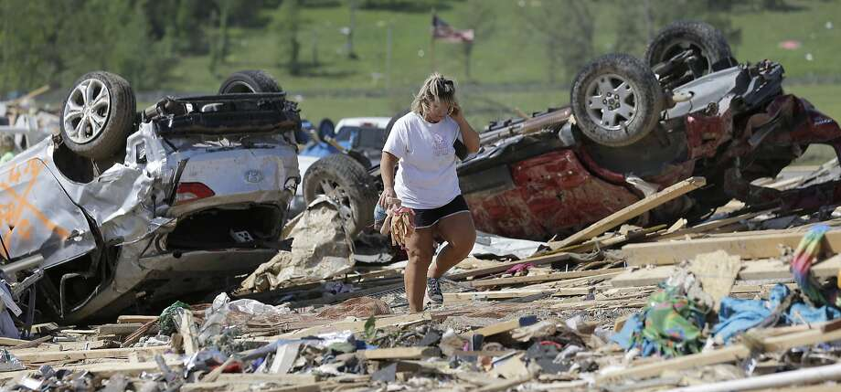 Connie Krehel walks through debris after her home was hit by a tornado in Vilonia, Ark., near Little Rock. The half-mile-wide twister killed at least 15 people. Photo: Eric Gay, Associated Press