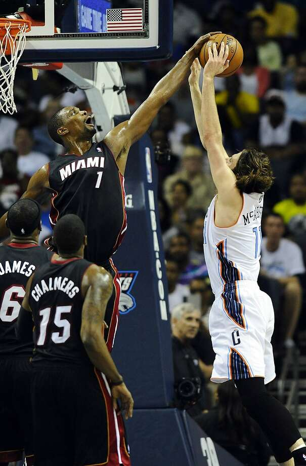 The Heat's Chris Bosh blocks Josh McRoberts' shot during the second half. The Heat finished off the sweep and have beaten Charlotte 20 straight times. Photo: David T. Foster III, McClatchy-Tribune News Service