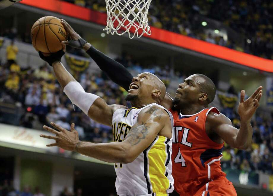 The Hawks' Paul Millsap, right, stops a drive by the Pacers' David West during a game in which Atlanta led by as many as 30 points before Indiana staged a mild comeback attempt in the fourth quarter. Photo: Darron Cummings, STF / AP