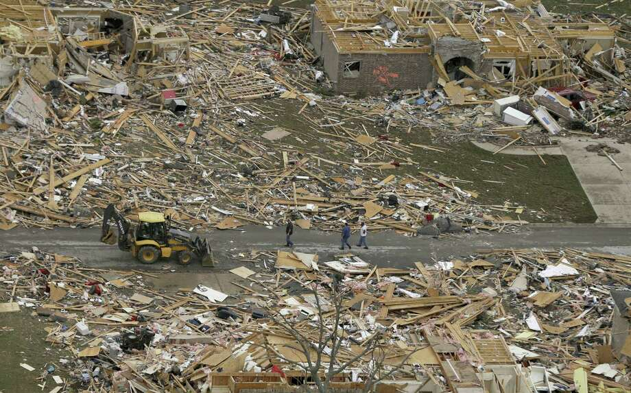 People walk between two destroyed houses in Mayflower, Ark., a day after a tornado struck. A tornado system continued to rip through the South, claiming victims in Mississippi and Alabama. Photo: Danny Johnston / Associated Press / AP