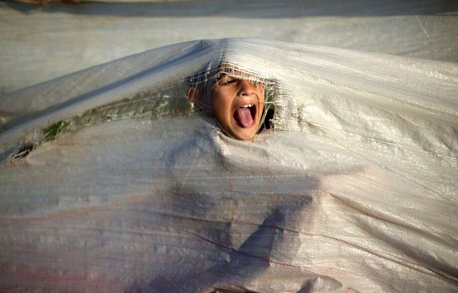 Rrrriiip!The head of a Palestinian boy pops through a tarp at the harbor in Gaza City. Photo: Mohammed Abed, AFP/Getty Images
