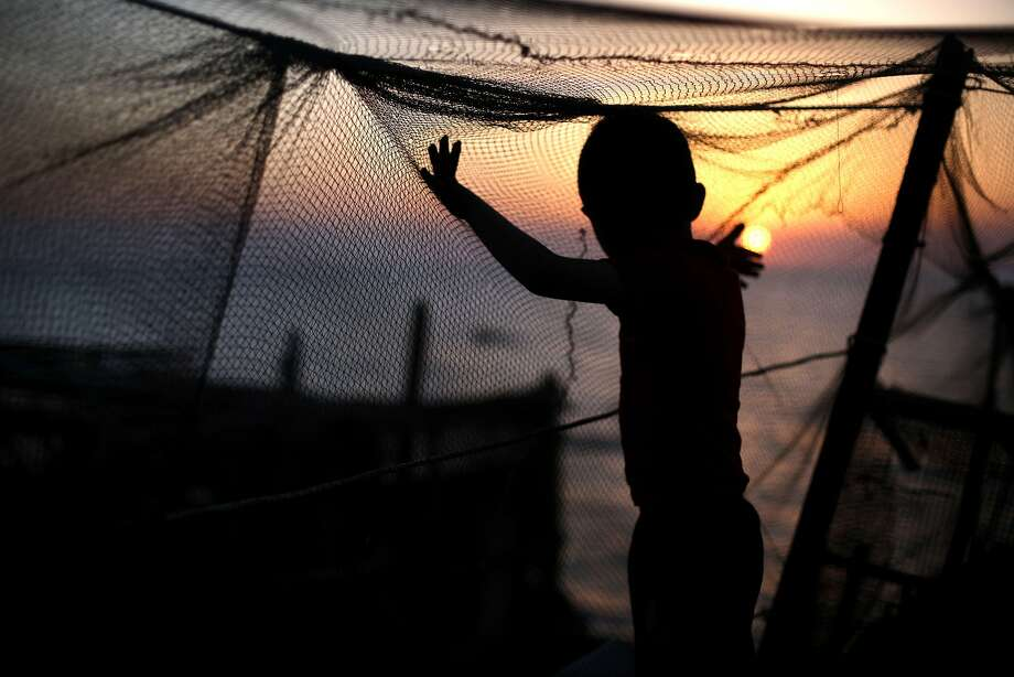 TOPSHOTS A Palestinian child plays with a fishing net as the sun sets over Gaza City on April 28, 2014. AFP PHOTO/MOHAMMED ABEDMOHAMMED ABED/AFP/Getty Images Photo: Mohammed Abed, AFP/Getty Images