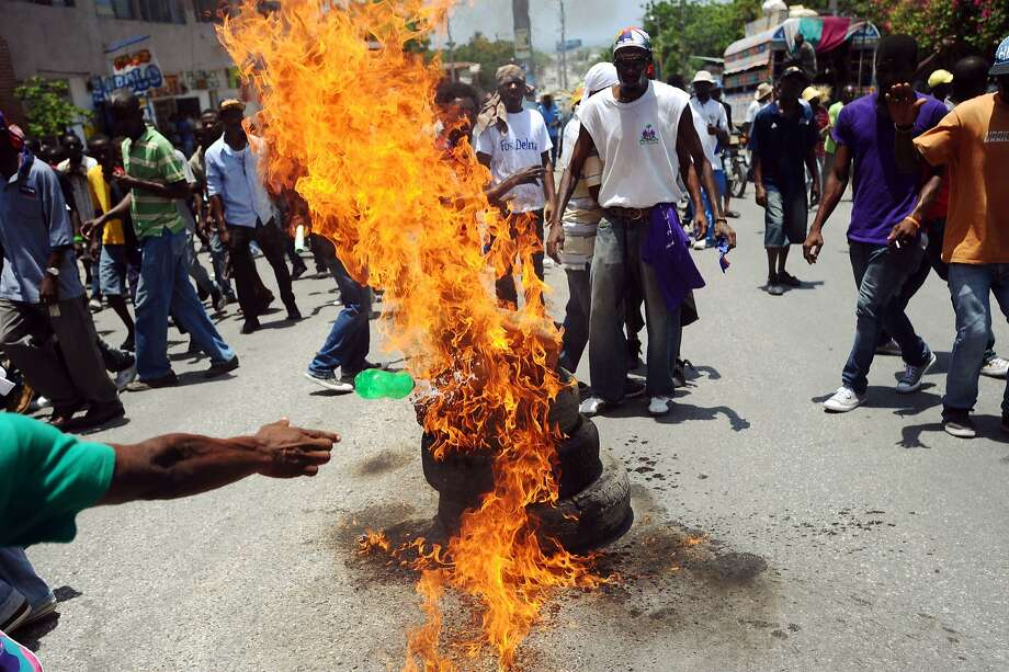 TOPSHOTS Protesters burn tires during a demonstration calling for the resignation of Haitian President Michel Martelly in Port-au-Prince on April 28, 2014. AFP PHOTO/Hector RETAMALHECTOR RETAMAL/AFP/Getty Images Photo: Hector Retamal, AFP/Getty Images