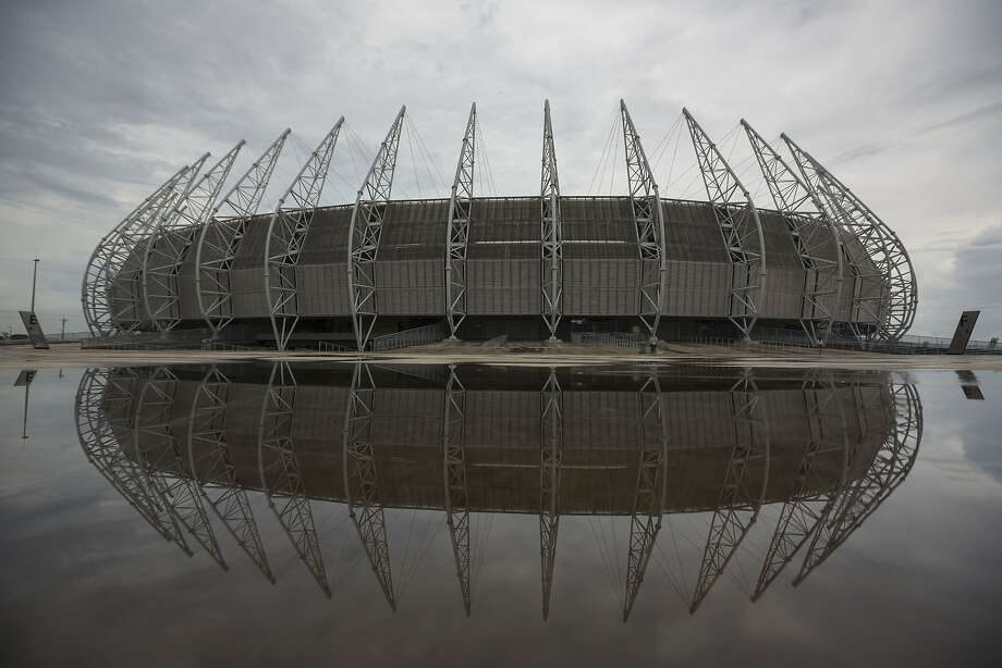 The Castelao stadium is reflected in water after heavy rains in Fortaleza, Brazil, Monday, April 28, 2014. Castelao will host matches during the 2014 World Cup soccer tournament. (AP Photo/Felipe Dana) Photo: Felipe Dana, Associated Press