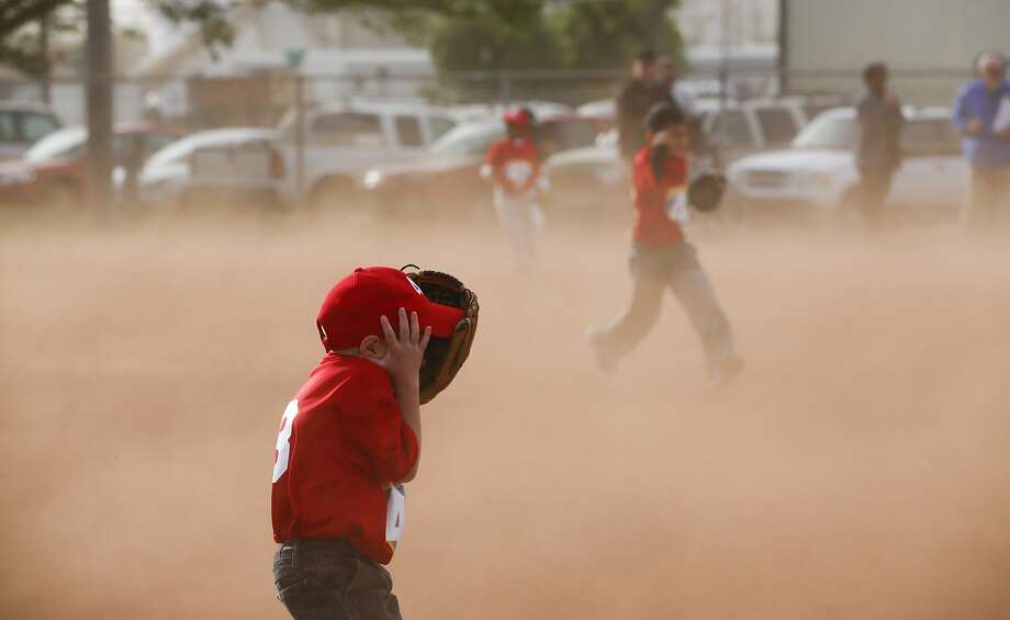 Austin Vanley, 5, covers his face from the flying sand while playing baseball in League 42's inaugural game Monday, April 28, 2014, in Wichita, Kan. National Weather Service in Wichita says the wind in Wichita got up to 52 mph. (AP Photo/The Wichita Eagle, Jaime Green) LOCAL TV OUT; MAGAZINES OUT; LOCAL RADIO OUT; LOCAL INTERNET OUT Photo: Jaime Green, Associated Press