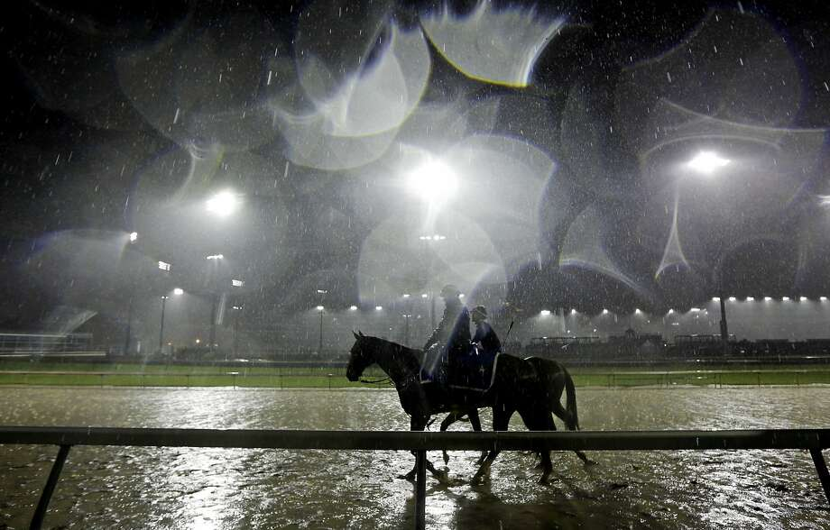 Exercise rider Abel Flores takes Kentucky Derby hopeful Tapiture for a morning workout in the rain at Churchill Downs Monday, April 28, 2014, in Louisville, Ky. (AP Photo/Morry Gash) Photo: Morry Gash, Associated Press