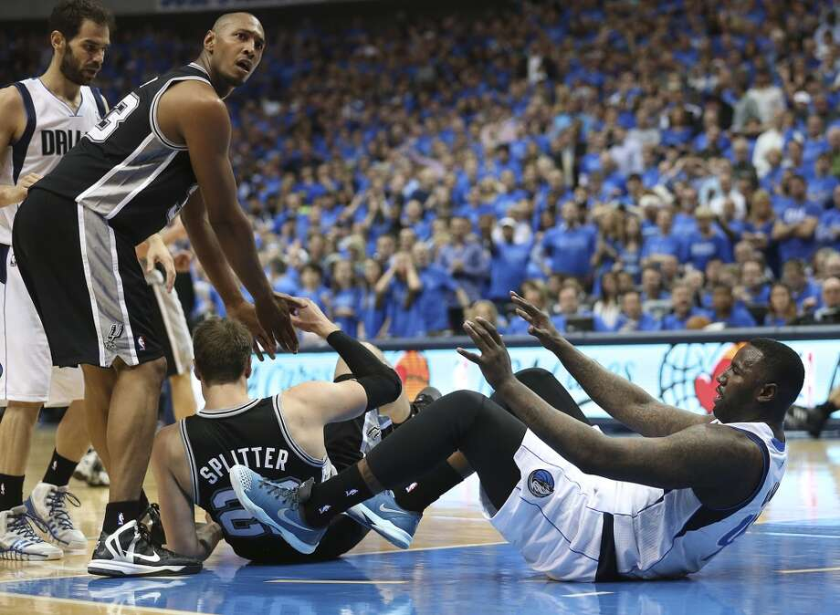 San Antonio Spurs' Boris Diaw looks over to an official as he helps Tiago Splitter after Dallas Mavericks' DeJuan Blair kicked him in the head during the second half of game four in the first round of the Western Conference Playoffs at the American Airlines Center in Dallas, Monday, April 28, 2014. DeJuan was ejected from the game. The Spurs won 93-89 to tie the series 2-2. Photo: Jerry Lara, San Antonio Express-News
