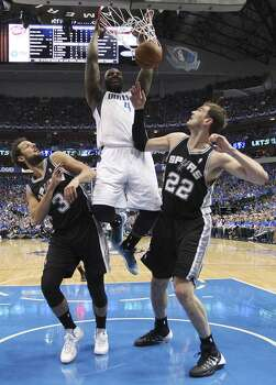 Dallas Mavericks' DeJuan Blair dunks the ball between San Antonio Spurs' Marco Belinelli, left,  and Tiago Splitter during the second half of game four in the first round of the Western Conference Playoffs at the American Airlines Center in Dallas, Monday, April 28, 2014. The Spurs won 93-89 to tie the series 2-2. Photo: Jerry Lara, San Antonio Express-News