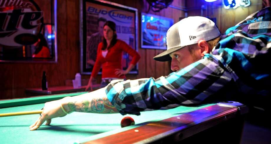 In a match with his wife Erica Phelps, Cody Phelps shoots pool at the Okee Dokee's Club on Monday. Guiseppe Barranco/The Enterprise Photo: Guiseppe Barranco/The Enterprise