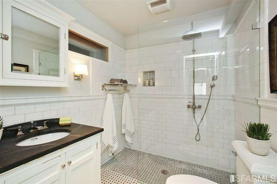 The upstairs bath is completely new but incorporates traditional elements like subway tile and basket weave marble floors. Photo: MLS