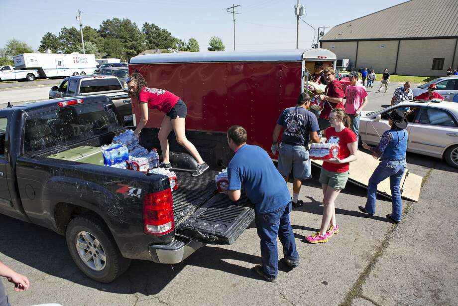 Volunteers load water at Beryl Baptist Church after a tornado yesterday tore through the area for the second time in three years, on April 28, 2014 in Vilonia, Arkansas. After deadly tornadoes ripped through the region, leaving more than a dozen dead, Mississippi, Arkansas, Texas, Louisiana and Tennessee are all under watch as multiple storms over the next few days are expected.  Photo: Wesley Hitt, Getty Images