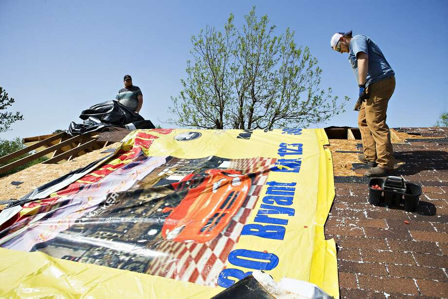Mitch Fortner and Cody Goff patch a roof with a billboard sign after a tornado yesterday tore through the area for the second time in three years, on April 28, 2014 in Vilonia, Arkansas. After deadly tornadoes ripped through the region, leaving more than a dozen dead, Mississippi, Arkansas, Texas, Louisiana and Tennessee are all under watch as multiple storms over the next few days are expected.  Photo: Wesley Hitt, Getty Images